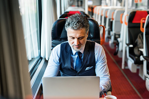 _0021_mature-businessman-with-laptop-travelling-by-train